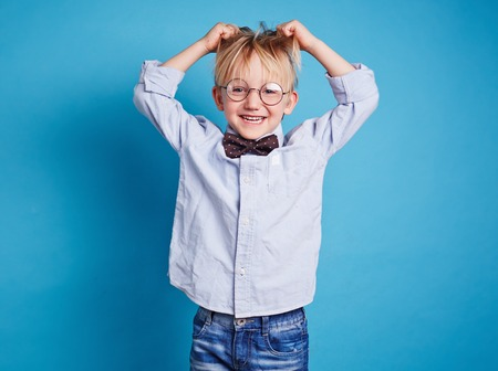 child boy: Little boy in eyeglasses and bowtie tousling his hair