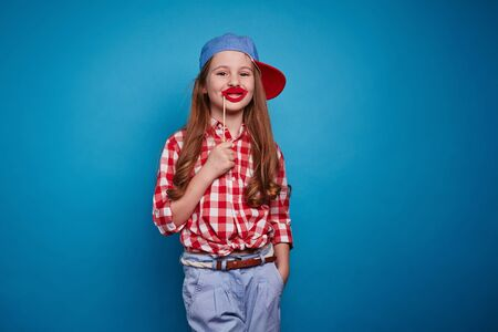 child smile: Cute girl holding red lips on stick by her mouth