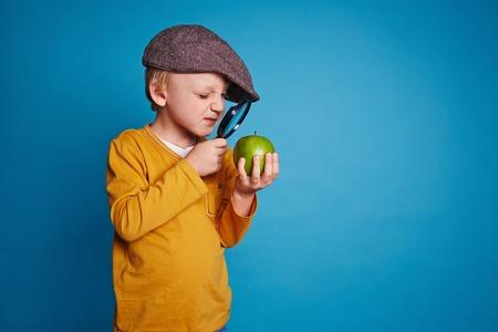 돋보기를 통해 녹색 사과를보고 어린 소년 스톡 콘텐츠