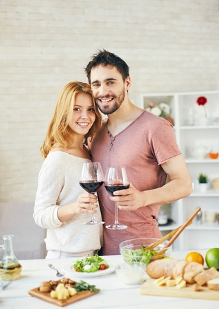 amorous woman: Amorous man and woman toasting with red wine in the kitchen Stock Photo