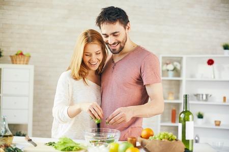 pareja saludable: Pareja joven que pone la lechuga cortada en un tazón