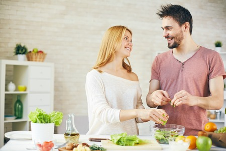 parejas: Joven pareja de cocinar el desayuno juntos