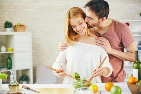 Aanhankelijk jonge man zoenen zijn vrouw terwijl ze koken salade