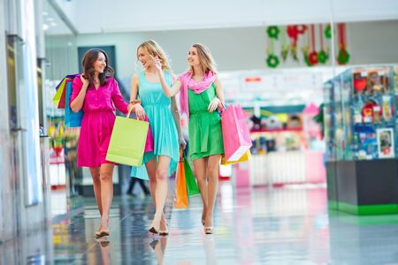 elegant dress: Beautiful girlfriends with paperbags shopping together