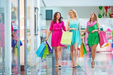shopaholism: Three girls in smart dressed walking down modern mall