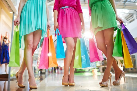 paperbags: Three modern girls in bright dresses and stylish shoes holding paperbags