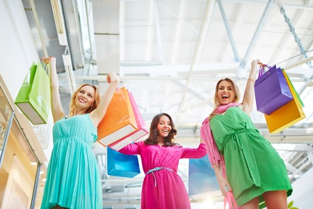 paperbags: Joyful shopaholics holding paperbags in raised hands