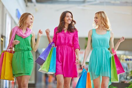 shopaholism: Glamorous girls talking while spending leisure in the mall