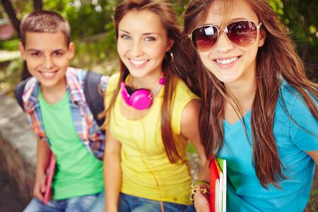 smiling teenagers: Happy teenage girls and guy looking at camera Stock Photo