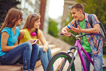 Happy guy on bicycle talking to pretty girls outside photo