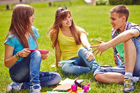 Friendly teenagers spending free time on green lawn photo