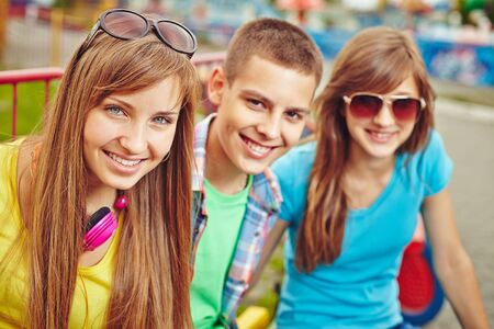 Happy teenage friends looking at camera outdoors photo