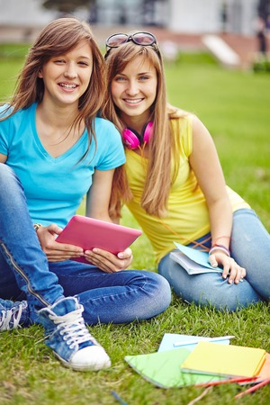 Teenage girls with touchpad relaxing on green lawn photo