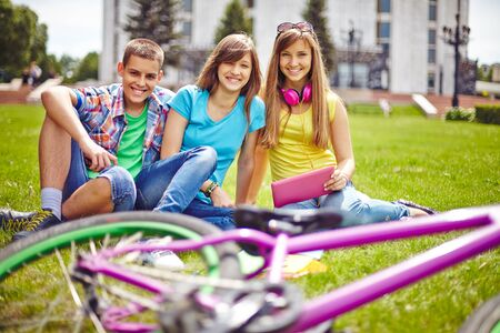 Cheerful teenage friends relaxing on green lawn in summer photo