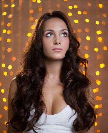 cabello rizado: Muchacha bonita con el pelo rizado largo en fondo chispeante