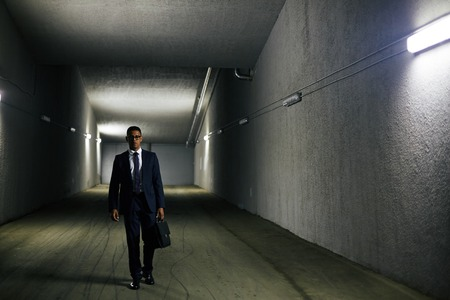 persons: Elegant businessman with briefcase walking down tunnel