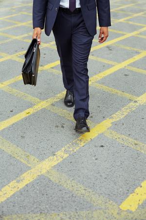 haste: Businessman in suit walking down trottoire