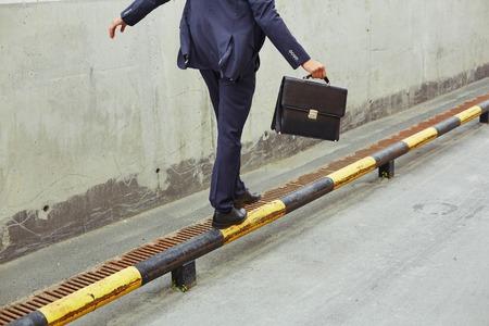 Achter mening van zakenman met aktentas balancing op geel-zwarte wegrand