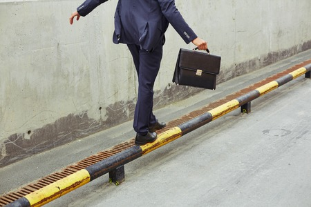 Rear view of businessman with briefcase balancing on yellow-and-black road curb