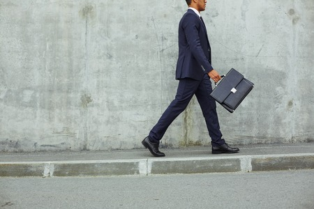 Successful businessman in suit walking along concrete wall in urban environment
