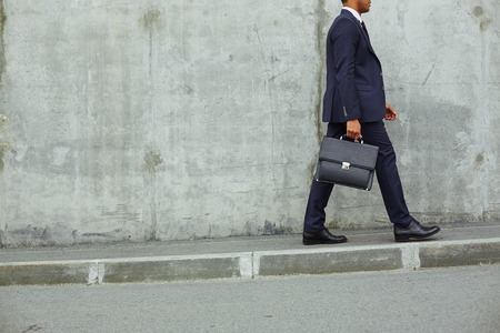 briefcase: Modern businessman with briefcase walking along concrete wall Stock Photo