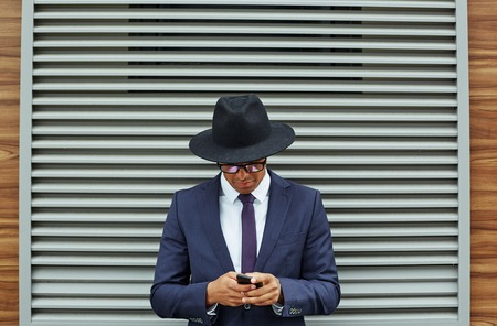 jalousie: Elegant businessman in suit, hat and eyeglasses using cellphone by jalousie