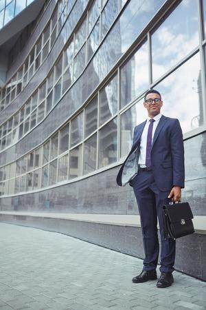 formalwear: Happy businessman in formalwear standing by modern building