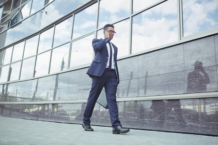 modern building: Young man in formalwear speaking on the phone while walking along modern building