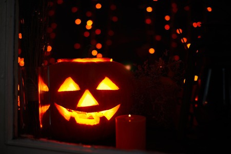 antichrist: Jack-o-lantern and burning candle near by Stock Photo