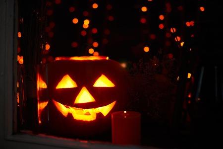 calabazas de halloween: Jack-o-linterna y vela encendida cerca Foto de archivo