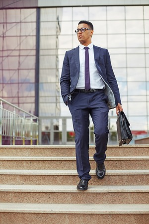 Young man in formalwear walking down stairs in urban environment Stock Photo