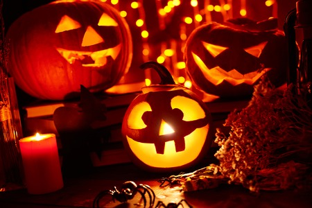 antichrist: Jack-o-lanterns, burning candle and Halloween spiders in darkness Stock Photo