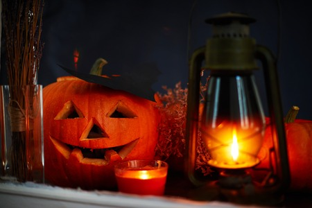 antichrist: Carved Halloween pumpkin with burning lantern and candle near by