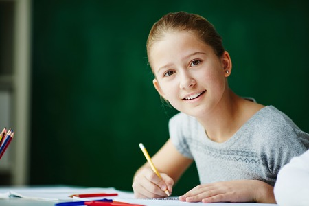child smile: Portrait of cute schoolgirl looking at camera while drawing
