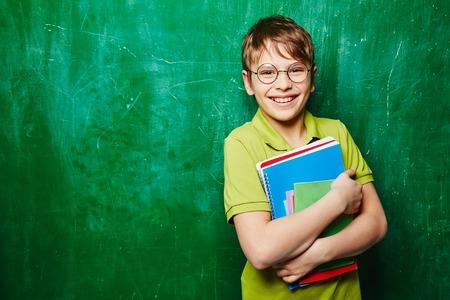 niños felices: Chico guapo con los libros que miran la cámara por la pizarra