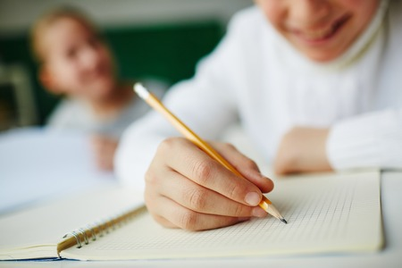 escribiendo: Kid celebración de lápiz y el dibujo en el bloc de notas