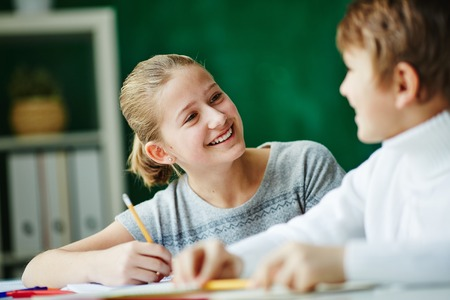 classmate: Happy schoolgirl looking at classmate while drawing Stock Photo