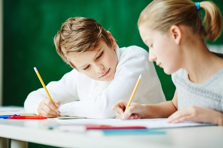 youthful: Youthful schoolkids drawing together at lesson
