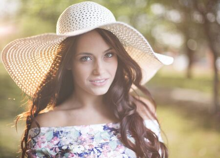 summer beauty: Beautiful girl in hat looking at camera outside