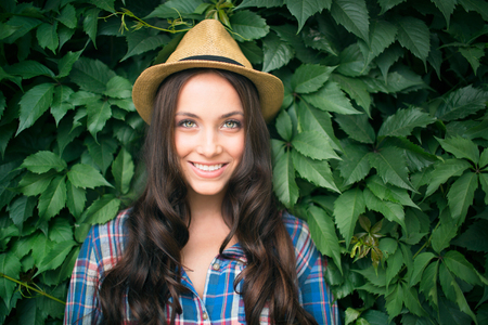 cowgirl hat: Happy female in cowgirl hat and shirt looking at camera by green plant