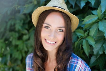 femmes souriantes: Bonne femme dans cowgirl chapeau regardant la caméra avec le sourire à pleines dents