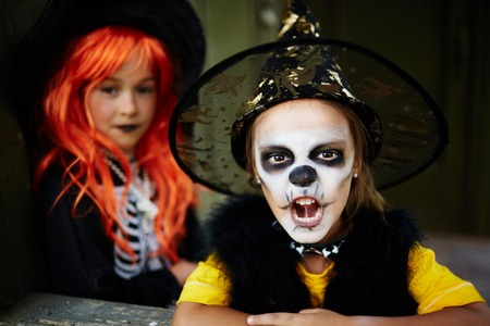 attire: Little girl in Halloween attire looking at camera with frightening expression Stock Photo