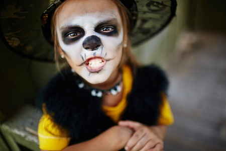 haunt: Halloween girl with painted face looking at camera