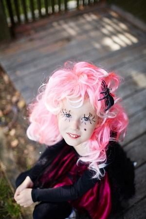 haunt: Halloween girl with spider in her pink hair looking at camera Stock Photo