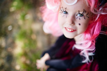 haunt: Smiling girl with pink wig and painted long eyelashes looking at camera