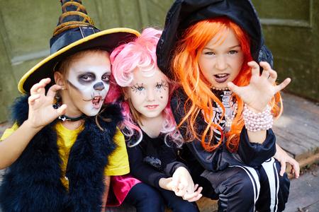 grupos de personas: Grupo de muchachas aterradoras en disfraces de Halloween que mira la cámara