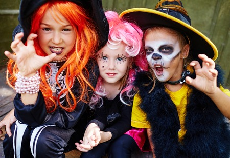 frightening: Little girls in Halloween costumes looking at camera with frightening expression Stock Photo