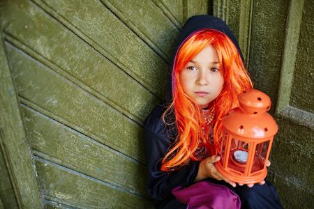 attire: Little girl in orange wig and Halloween attire holding lantern