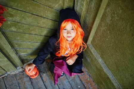 repent: Youthful girl in Halloween attire looking at camera while sitting by wall of haunted house