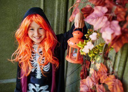 attire: Cheerful girl in Halloween attire with lantern looking at camera